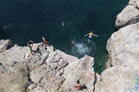 A youth jumps in the sea from a rock at Varkiza village, a few miles southwest of Athens, on Thursday, July 29, 2021. One of the most severe heat waves recorded since 1980s scorched southeast Europe on Thursday, sending residents flocking to the coast, public fountains and air-conditioned locations to find some relief, with temperatures rose above 40 C (104 F) in parts of Greece and across much of the region. (AP Photo/Yorgos Karahalis)