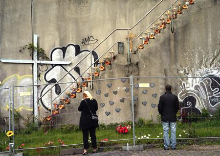 Wooden crosses with names of victims of Love Parade stampede stand on steps at site of disaster in Duisburg