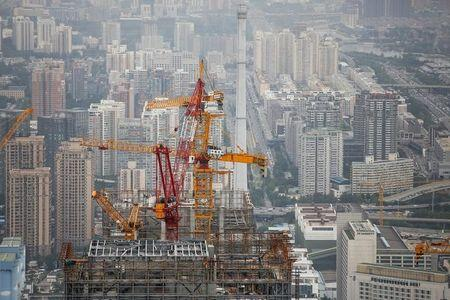 Cranes are seen on top of a skyscraper that is under construction in Beijing