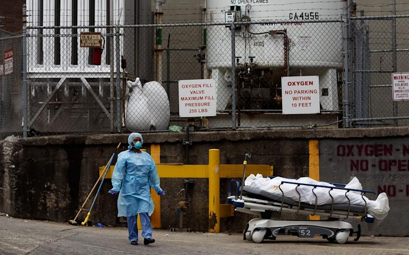 A medical professional stands with a body on a hospital gurney as it is moved to be temporarily stored in a mobile morgue, put in place due to lack of space at the hospital, outside of the Brooklyn Hospital Center in Brooklyn, New York - Shutterstock