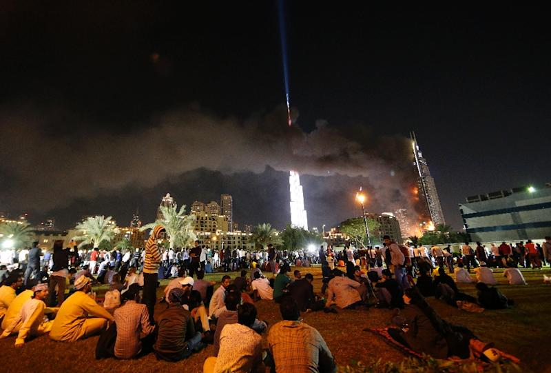 People watch the Address Downtown hotel burning after a huge fire ripped through the luxury hotel in Dubai on December 31, 2015 (AFP Photo/KARIM SAHIB)