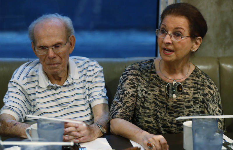 In this, Monday, Oct. 7, 2019 photo, Vera Karliner, right, speaks during an interview with The Associated Press in Aventura, Fla., along with her husband Herb, left, who was on the ship named the St. Louis that was full of Jewish refugees but was turned away from the U.S. in 1939. Aging Holocaust survivors are trying to recover insurance benefits that were never honored by Nazi-era companies, which could be worth billions of dollars. The companies have demanded original paperwork, such as death certificates, that were not available after World War II. The survivors want to take insurance companies to court in the U.S. to recover the money, but it would take an act of Congress to allow it. (AP Photo/Wilfredo Lee)