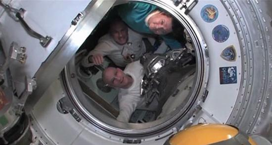 Expedition 31 commander Oleg Kononenko of Russia (top), Dutch astronaut Andrew Kuipers (center) and NASA astronaut Don Pettit bid farewell to their crewmates on the International Space Station just before shutting the hatches between their Soyu