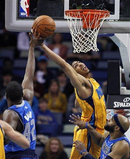 New Orleans Hornets forward Anthony Davis, center, drives to the basket against the Dallas Mavericks forward Elton Brand (42) in the first half of an NBA basketball game in New Orleans, Friday, Feb. 22, 2013. (AP Photo/Gerald Herbert)