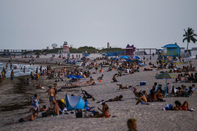 People relax on the beach in Miami Beach, Florida -- a state seeing record numbers of COVID-19 deaths (AFP Photo/CHANDAN KHANNA)