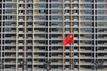 Chinese flag flutters in front of a residential building under construction in Huaian
