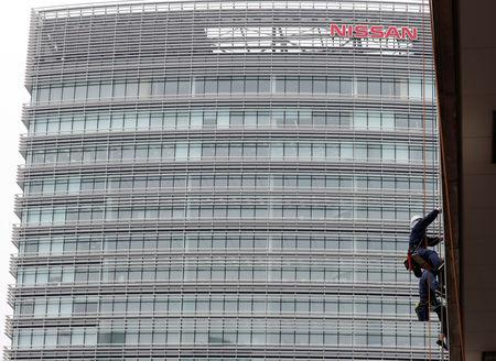 FILE PHOTO: Window cleaners are seen in front of Nissan Motor Co.'s global headquarters building in Yokohama, Japan November 22, 2018.   REUTERS/Toru Hanai