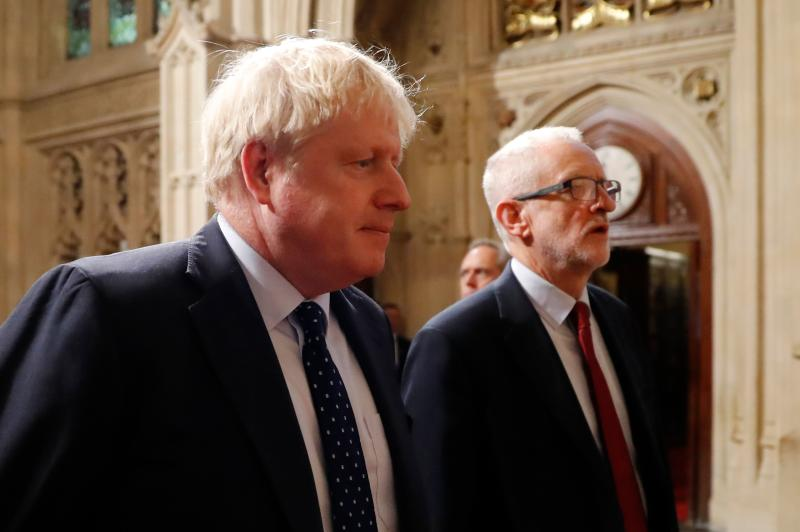 Britain's Prime Minister Boris Johnson (L) and main opposition Labour Party leader Jeremy Corbyn (R) head the procession of members of parliament through the Peers Lobby into the House of Lords to listen to the Queen's Speech during the State Opening of Parliament in the Houses of Parliament in London on October 14, 2019. - The State Opening of Parliament is where Queen Elizabeth II performs her ceremonial duty of informing parliament about the government's agenda for the coming year in a Queen's Speech. (Photo by Tolga AKMEN / POOL / AFP) (Photo by TOLGA AKMEN/POOL/AFP via Getty Images)