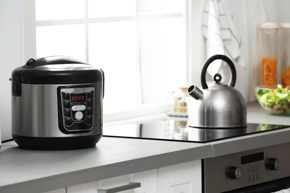 Modern electric multi cooker on kitchen countertop near stove