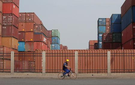 A worker cycles past containers outside a logistics center near Tianjin Port, in northern China, May 16, 2019. REUTERS/Jason Lee/Files