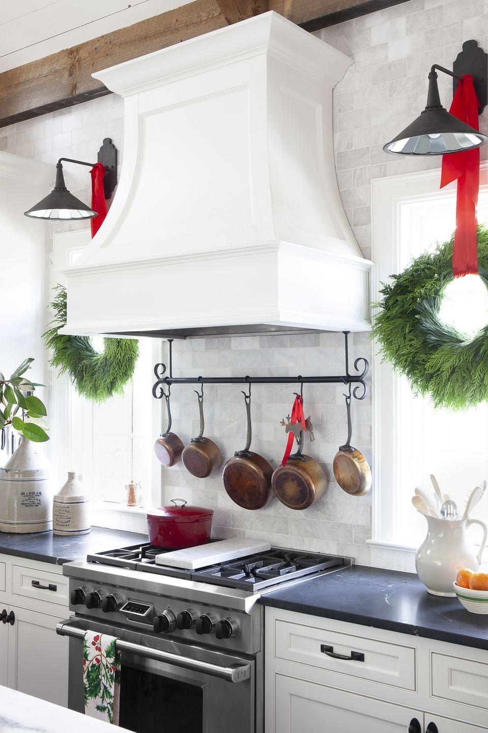 <p>The perfect example of the use-what-you-have spirit! Get creative with natural places to hang wreaths over windows. Here, red ribbon is tied in a simple bow over the kitchen's black sconces. </p>