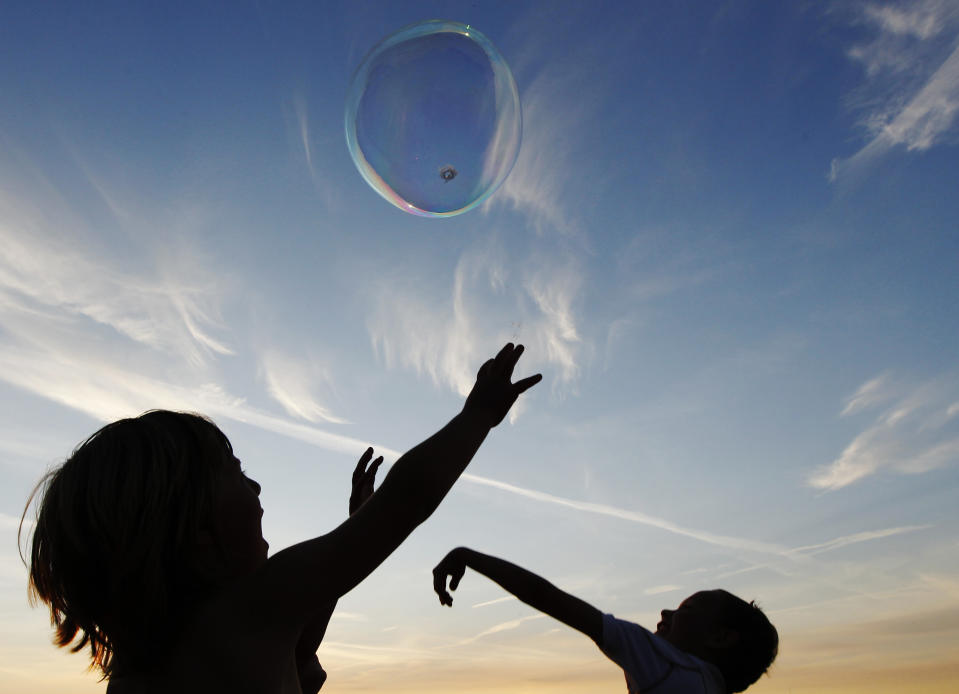 Children play with giant bubbles at the Glastonbury Festival 2010 in south west England, June 23, 2010. Picture taken June 23, 2010. REUTERS/Luke MacGregor (BRITAIN - Tags: ENTERTAINMENT SOCIETY)