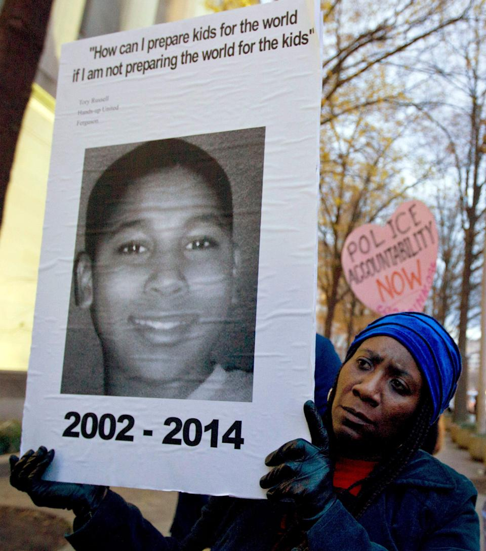 Tomiko Shine holds up a picture of Tamir Rice during a protest in Washington, D.C. Rice was fatally shot by a rookie police officer in Cleveland on Nov. 22, 2014. The 12-year-old was holding a toy gun while playing in the park when he was shot and killed.
