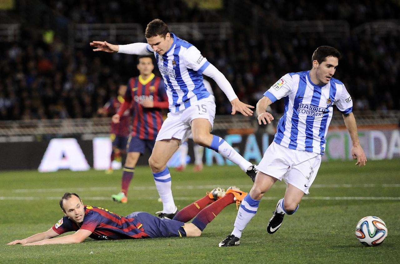 FC Barcelona's Andres Iniesta, left, is tackled by Real Sociedad's Mikel Gonzalez, right, and falls inside of penal area,  during their Spanish Copa del Rey semifinal second leg soccer match against Real Sociedad, at Anoeta stadium, in San Sebastian northern Spain, Wednesday, Feb. 12, 2014. (AP Photo/Alvaro Barrientos)
