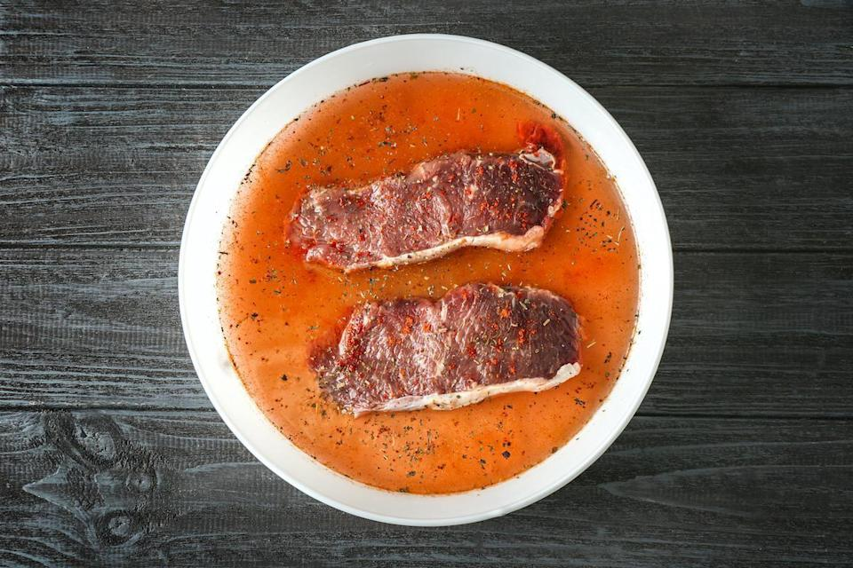 "<p>For less tender steaks like flank, skirt or round, Wasser suggests a tenderizing marinade that contains acidic ingredients such as lemon juice, flavored vinegar <a href=""https://www.thedailymeal.com/cook/unusual-meat-marinades?referrer=yahoo&category=beauty_food&include_utm=1&utm_medium=referral&utm_source=yahoo&utm_campaign=feed"" rel=""nofollow noopener"" target=""_blank"" data-ylk=""slk:or even Dr. Pepper"" class=""link rapid-noclick-resp"">or even Dr. Pepper</a> as well as natural enzymes like ginger or pineapple. Allow a fourth- to a half-cup of marinade for every pound of beef and marinate for six to 12 hours in the refrigerator — never at room temperature. Dry rubs and marinades work best when cooking beef on a grill, Wasser says. Avoid pastes or marinades with high sugar content to minimize burning.</p>"