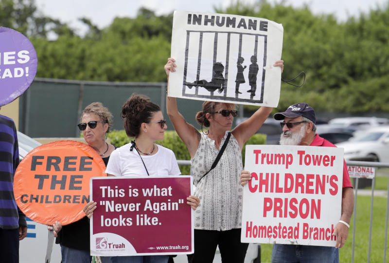 FILE - In this July 15, 2019, file photo, protesters hold signs outside of the Homestead Temporary Shelter for Unaccompanied Children while members of Congress tour the facility in Homestead, Fla. The government will be able to hold immigrant children detained at the Mexican border for a longer period of time under a move by the Trump administration. (AP Photo/Lynne Sladky, File)