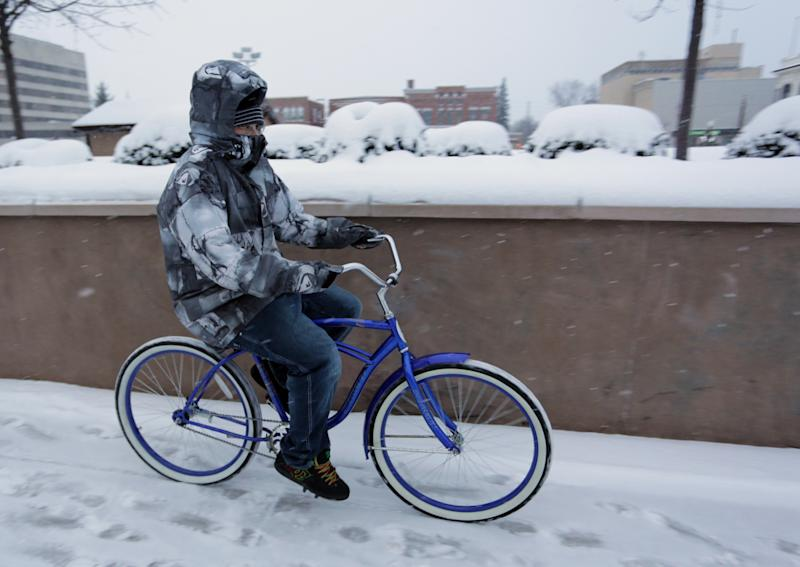 A bundled-up man rides a bike in snowy Wausau, Wis., Sunday, Dec. 22, 2013. Wausau was on the edge of a large snowstorm and areas to the south of the north-central Wisconsin community received much more snow. (AP Photo/Daily Herald Media, Dan Young)
