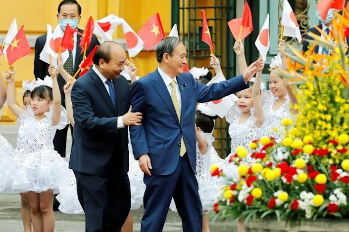 Japanese Prime Minister Yoshihide Suga (R, with his Vietnamese counterpart Nguyen Xuan Phuc) said Tokyo had agreed to step up defence cooperation with Hanoi