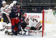 Chicago Blackhawks' Kevin Lankinen, right, covers the puck as teammate Kirby Dach, left, and Columbus Blue Jackets' Cam Atkinson, left center, and Jack Roslovic fight for position during the second period of an NHL hockey game Saturday, April 10, 2021, in Columbus, Ohio. (AP Photo/Jay LaPrete)