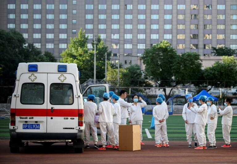 Medical personnel wearing protective suits gathered before swab tests for people who visited or live near the market, which supplies most of Beijing's fresh produce (AFP Photo/NOEL CELIS)