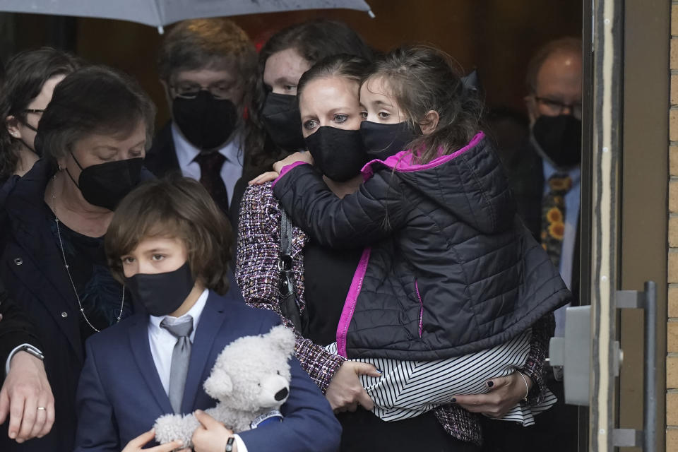 """Shannon Terranova, center right, wife of the late U.S. Capitol Police officer William """"Billy"""" Evans, carries her daughter Abigail Evans, 7, right, while walking with her son Logan Evans, 9, front left, and Evan's mother Janice Evans, left, as they depart St. Stanislaus Kostka Church following a funeral Mass for her husband, in Adams, Mass., Thursday, April 15, 2021. Evans, a member of the U.S. Capitol Police, was killed on Friday, April 2, when a driver slammed his car into a checkpoint he was guarding at the Capitol. (AP Photo/Steven Senne)"""