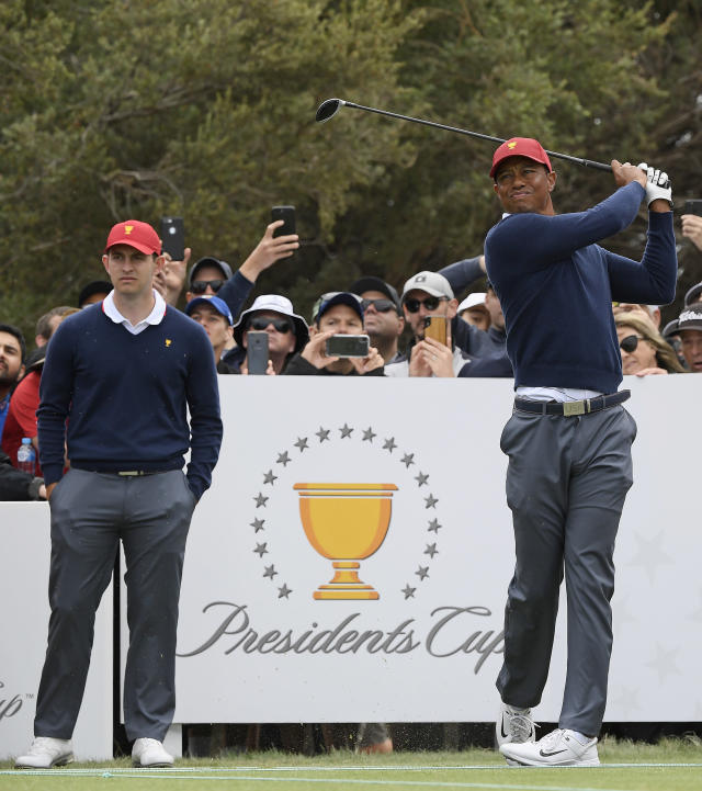 USA's Patrick Cantlay, left, watches as captain Tiger Woods tees off during a practice session ahead of the President's Cup Golf tournament in Melbourne, Tuesday, Dec. 10, 2019. (AP Photo/Andy Brownbill)