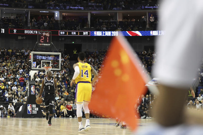 "In this Thursday, Oct. 10, 2019, photo, Brooklyn Nets' Theo Pinson, left, drives against Los Angeles Lakers' Danny Green, right, near a Chinese national flag during a preseason NBA game at the Mercedes Benz Arena in Shanghai, China. When Houston Rocket's general manager Daryl Morey tweeted last week in support of anti-government protests in Hong Kong, everything changed for NBA fans in China. A new chant flooded Chinese sports forums: ""I can live without basketball, but I can't live without my motherland."" (AP Photo, File)"