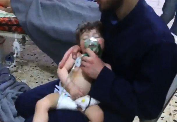 PHOTO: An image grab taken from a video released by the Syrian civil defense in Douma shows an unidentified volunteer holding an oxygen mask over a child's face at a hospital following a reported chemical attack on the rebel-held town, April 8, 2018. (AFP/HO/Syria Civil Defense/Getty Images)