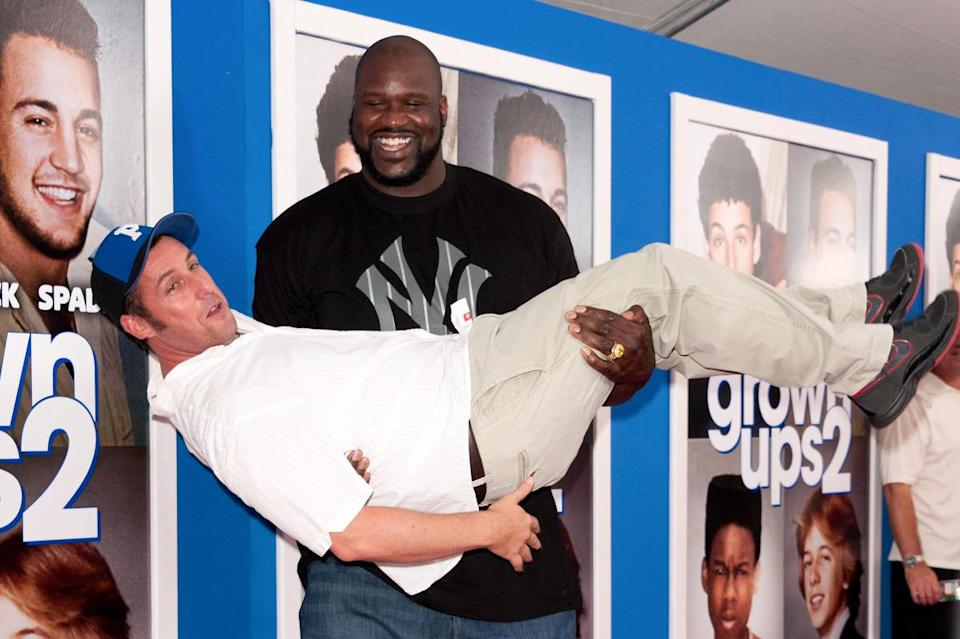 """Shaquille O'Neal holding Adam Sandler in his arms like a baby at the premiere of """"Grown Ups 2"""" on July 10, 2013 in New York City"""
