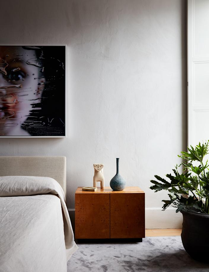 Under the Marilyn Minter portrait, the Milo Baughman bedside table holds an Italian vase and a 1970s limestone lamp by the French designer Alfred Tormos, from Glen Dooley Antiques.