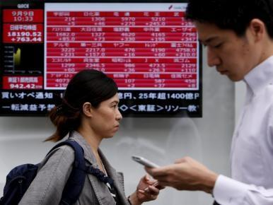 Pedestrians holding their mobile phone walk past an electronic board showing the various stock prices outside a brokerage in Tokyo