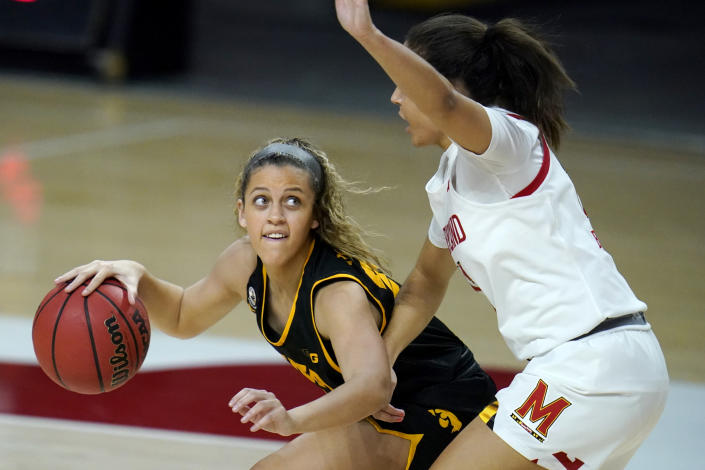 Iowa guard Gabbie Marshall, left, works the floor against Maryland guard Katie Benzan during the first half of an NCAA college basketball game, Tuesday, Feb. 23, 2021, in College Park, Md. (AP Photo/Julio Cortez)