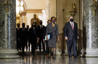 Clerk of the House Cheryl Johnson along with acting House Sergeant-at-Arms Tim Blodgett, lead the Democratic House impeachment managers as they walk through Statuary Hall in the Capitol, to deliver to the Senate the article of impeachment alleging incitement of insurrection against former President Donald Trump, Monday, Jan. 25, 2021 in Washington. (AP Photo/Susan Walsh)