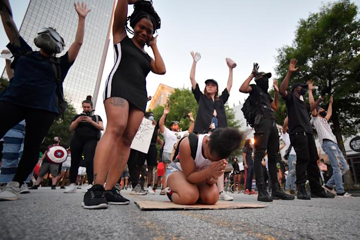 Demonstrators pray during a march, Sunday, May 31, 2020, in Atlanta. Protests continued following the death of George Floyd, who died after being restrained by Minneapolis police officers on May 25. (AP Photo/Mike Stewart)