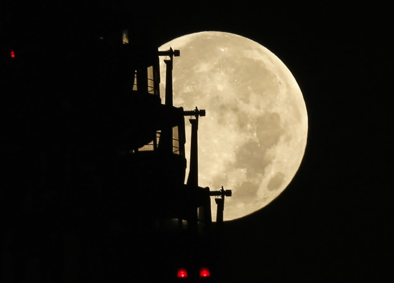 The supermoon is seen behind a ferris wheel in Tokyo August 11, 2014. The astronomical event occurs when the moon is closest to the Earth in its orbit, making it appear much larger and brighter than usual. REUTERS/Toru Hanai (JAPAN - Tags: ENVIRONMENT SOCIETY)