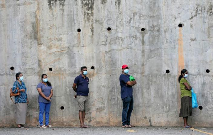 FILE PHOTO: People maintain the one-meter distance in-between each other as they stand in a line to buy groceries at a supermarket during the time government lifted the curfew in Colombo