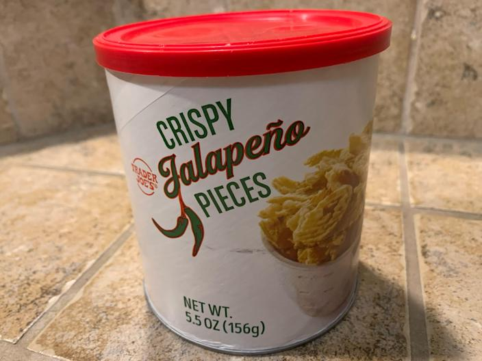 Trader joe's crispy jalepeno pieces in its original white and red container against beige tile