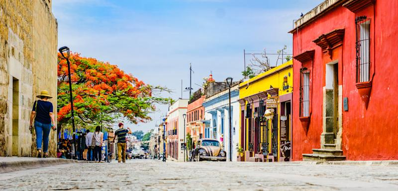 Oaxaca, Mexico on 24th April 2016: View on street with Colorful colonial buildings in th eold town with a group of people