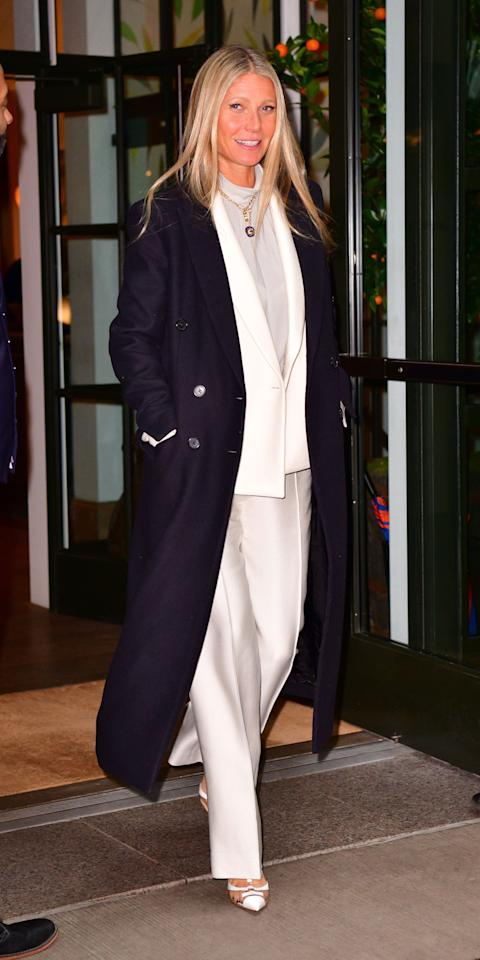 <p>Gwyneth Paltrow kept warm in frigid New York City by layering a navy coat over a white pants suit and gray turtleneck. A pendant necklace and white pumps with clear panels solidified her perfect winter outfit.</p>