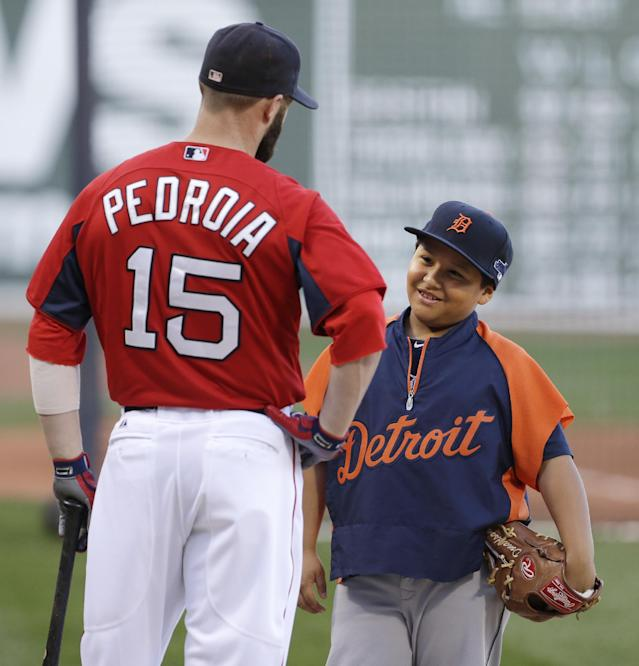 Victor Jose Martinez, son of Detroit Tigers designated hitter Victor Martinez, talks with Boston Red Sox second baseman Dustin Pedroia (15) during a baseball workout at Fenway Park in Boston, Friday, Oct. 11, 2013. The Red Sox will face the Tigers in Game 1 of the American League championship series on Saturday. (AP Photo/Charlie Riedel)