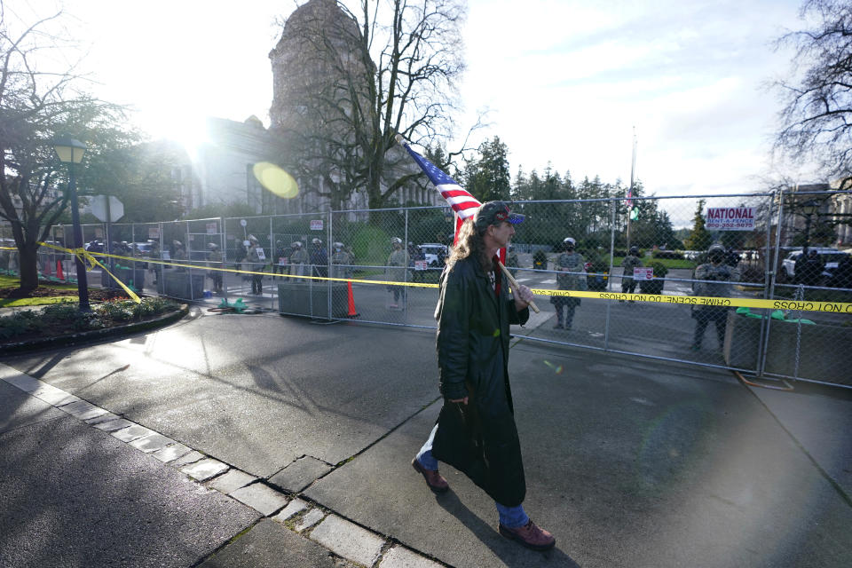 A man carries a U.S. flag past National Guard members standing behind a perimeter fence, Sunday, Jan. 10, 2021, at the Capitol in Olympia, Wash. With the FBI warning of potential violence at all state capitols Sunday, Jan. 17, the ornate halls of government and symbols of democracy looked more like heavily guarded U.S. embassies in war-torn countries. (AP Photo/Ted S. Warren)