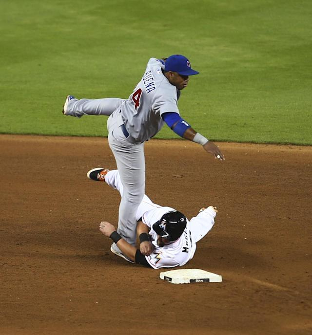 After tagging Miami Marlins runner Casey McGehee (9) out Chicago Cubs' Luis Valbuena (24) is unable to get a double play during the fifth inning of a baseball game in Miami, Tuesday, June 17, 2014. (AP Photo/J Pat Carter)