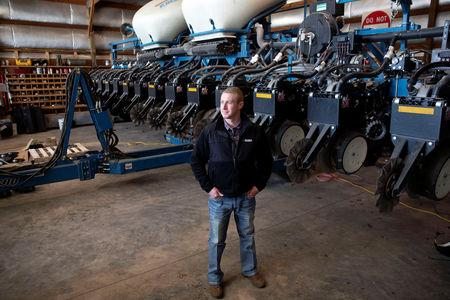 Soybean farmer Austin Rincker poses for a photograph near his planter equipment at his farm in Moweaqua, Illinois, U.S., March 6, 2019. Rincker will farm approximately 2500 acres in the upcoming season, split evenly between corn and soybeans. Picture taken March 6, 2019. REUTERS/Daniel Acker
