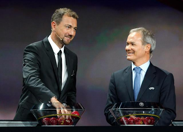 Former Polish goalkepper Jerzy Dudek, left, prepares the draw as UEFA Director of competitions Giorgio Marchetti looks on, during the Europa League draw ceremony of the first round of the 2014/2015 Europa League, at the Grimaldi Forum in Monaco, Friday, Aug. 29, 2014. (AP Photo/Claude Paris)