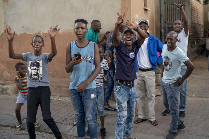 Young residents of the densely populated Alexandra township east of Johannesburg cheer at the photographer following a South African National Defense Forces patrol Friday, March 27, 2020. South Africa went into a nationwide lockdown for 21 days in an effort to mitigate the spread to the coronavirus, but in Alexandra, many people were gathering in the streets disregarding the lockdown. The new coronavirus causes mild or moderate symptoms for most people, but for some, especially older adults and people with existing health problems, it can cause more severe illness or death.(AP Photo/Jerome Delay)
