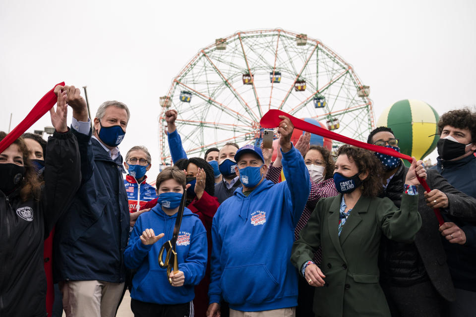 New York City Mayor Bill de Blasio, left, attends the ribbon cutting and seasonal opening of the Coney Island amusement park area, Friday, April 9, 2021, in the Brooklyn borough of New York. Coney Island's illustrious amusement parks are reopening Friday after the coronavirus pandemic shuttered them all last year. (AP Photo/John Minchillo)