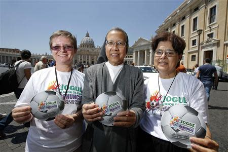 """Nuns Bottani, Castalone and Sammut hold the logo of an international campaign called """"Play in Favour of Life-Denounce Human Trafficking,"""" on the risks they say will be associated with the June-July games, as they pose in front of Saint Peter's basilica in"""