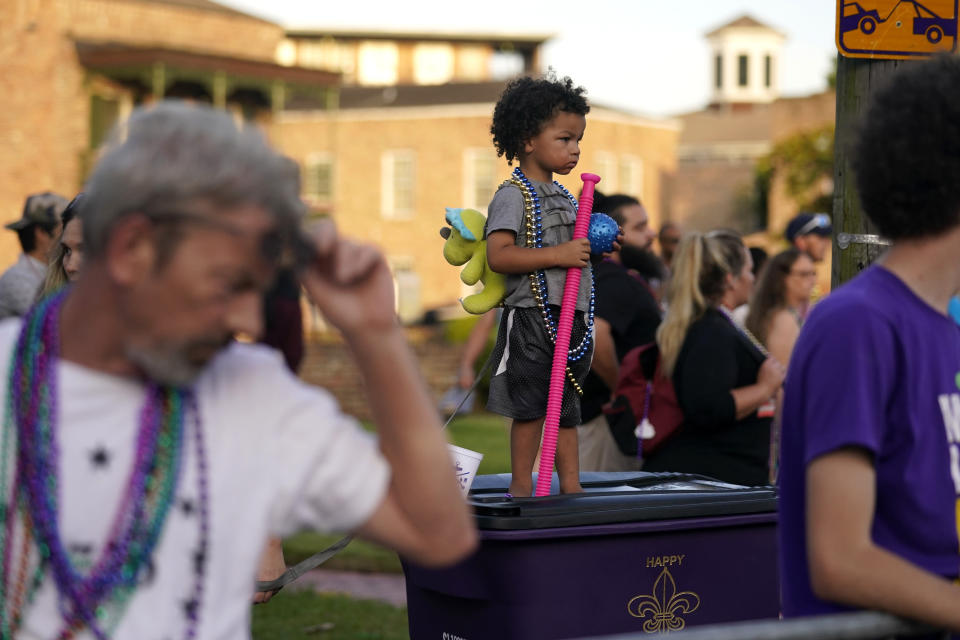 """Xeavier Domingue, 2, stands on a trash can to catch throws during a parade dubbed """"Tardy Gras,"""" to compensate for a cancelled Mardi Gras due to the COVID-19 pandemic, in Mobile, Ala., Friday, May 21, 2021. (AP Photo/Gerald Herbert)"""