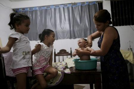 Gabriela Alves de Azevedo bathes her four-month-old daughter Ana Sophia, who was born with microcephaly, at their house in Olinda, Brazil, March 2, 2016. REUTERS/Ueslei Marcelino/Files