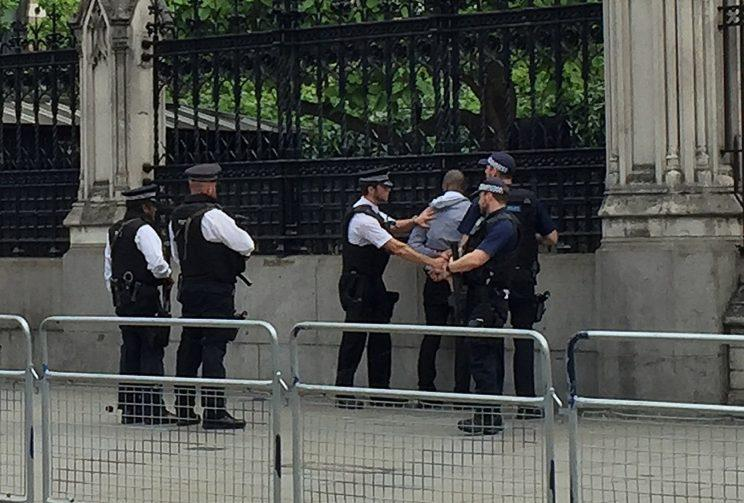 Police detain a man outside the Palace of Westminster
